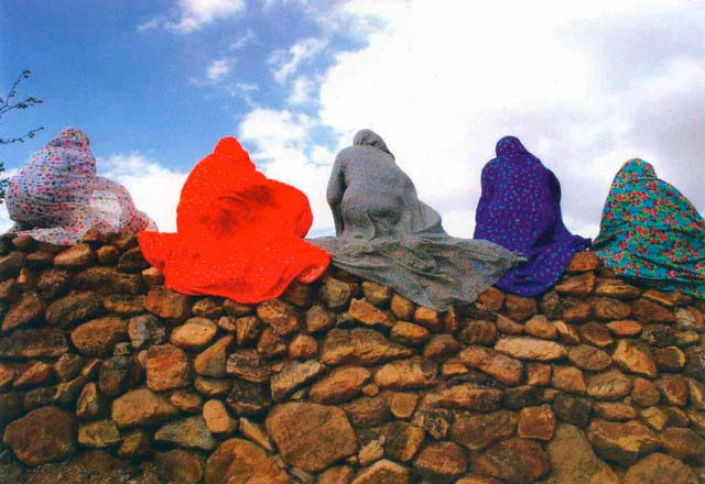 Five Iranian Women in Colorful Chadors (Islamic gowns) Sit on Stone Wall