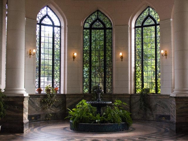 Indoor Fountain in Front of Ornate Windows